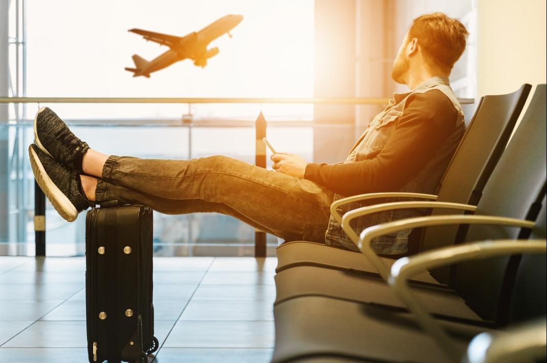 homem sentado com as pernas em cima de uma mala observa um avião decolando