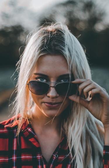 42e244ae5 mulher de frente para a câmera olha por cima de óculos de sol feminino