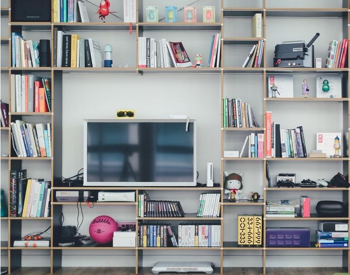 televisão de tela plana em uma estante cheia de nichos el ivros