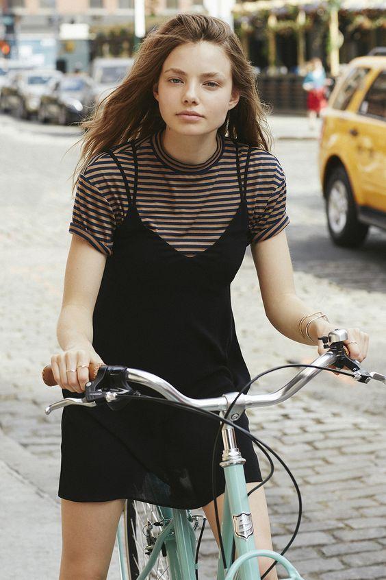 menina com vestido e camiseta andando de bicicleta