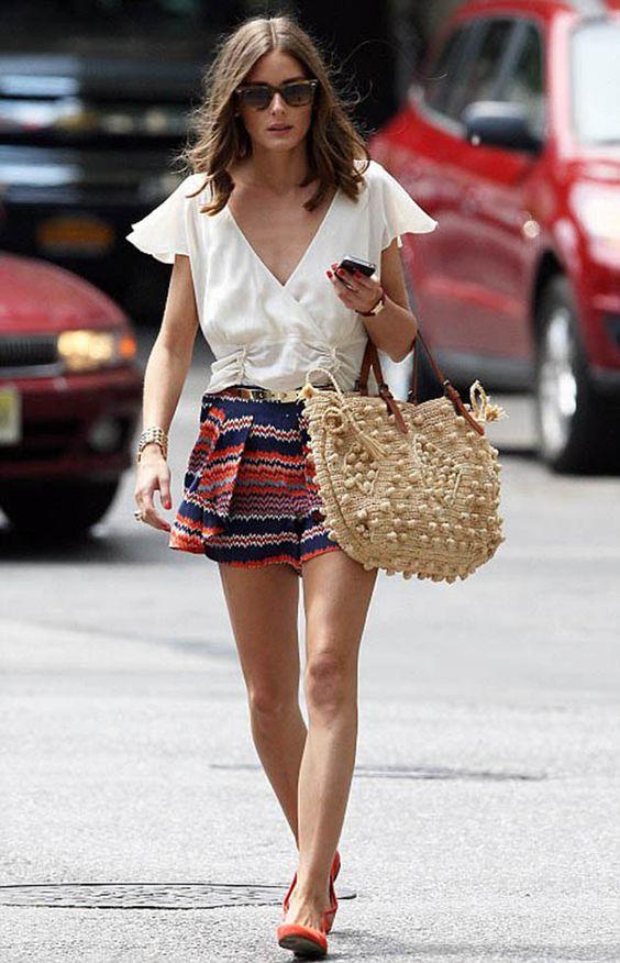 mulher com blusa branca e short anda com bolsa de palha