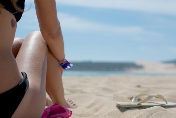 mulher de biquini sentada na areia