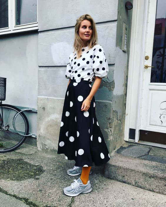 mulher com camisa e saia longa estampada com poás