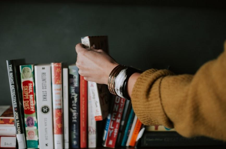 braço de mulher mexe em uma fileira de livros