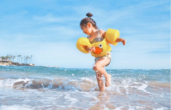 criança com boia brinca na beira do mar