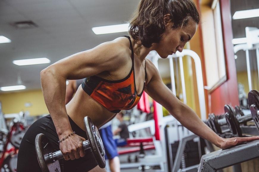 Mulher levantando peso na academia