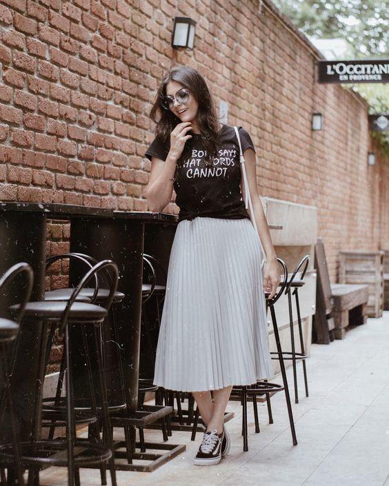 mulher usando t-shirt, saia plissada e tenis vans
