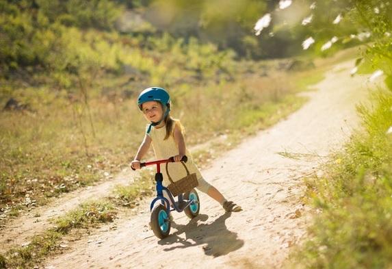 menina com bicicleta e capacete parada em paisagem
