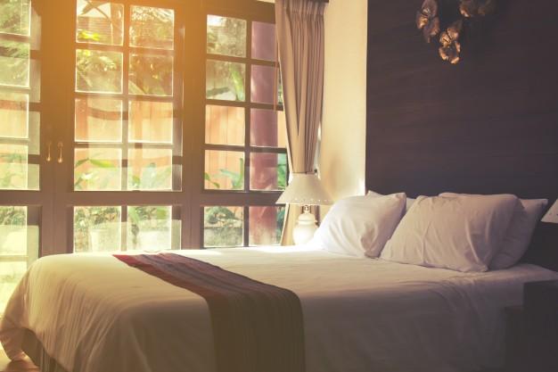 cama de casal com colcha e travesseiros brancos, abajur em frente a porta de madeira e vidro