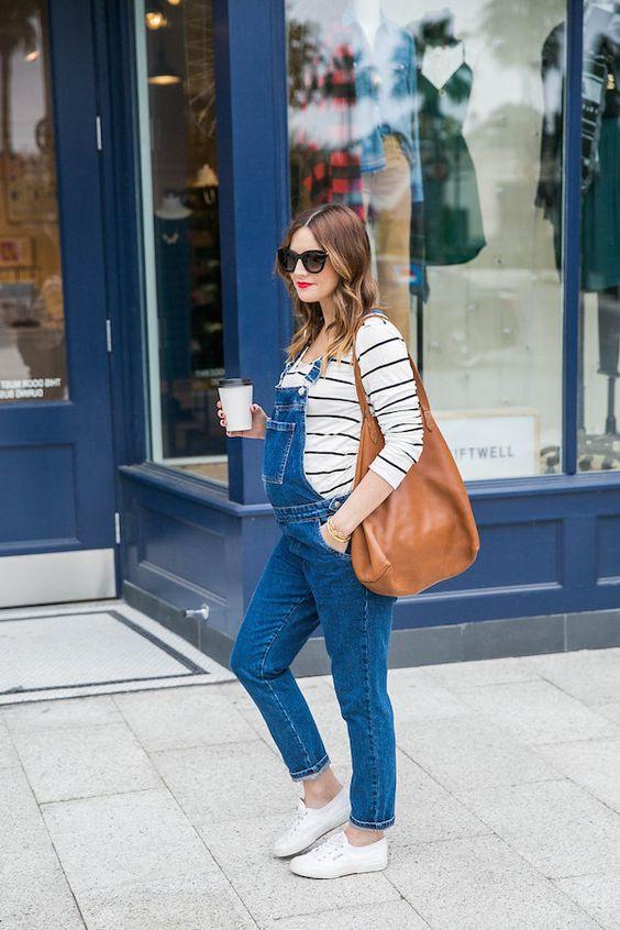 mulher grávida de macacão jeans, tênis brancos, blusa listrada e óculos escuros