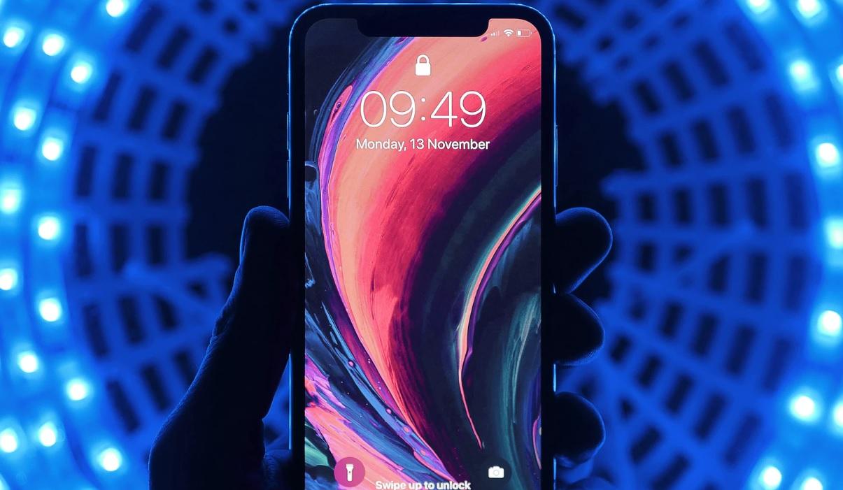 close de uma mão segurando um celular em pé